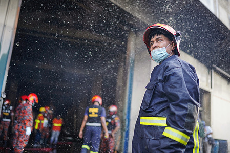 Firefighters are seen around the building after a fire broke out at a factory named Hashem Foods Ltd in Rupganj of Narayanganj district on the outskirts of Dhaka. At least 52 people have been found dead, 25 others injured and many are feared trapped after a massive fire raged through a factory, the cause of the fire which originated at a ground floor of a multi storey building of the factory is not yet known.
