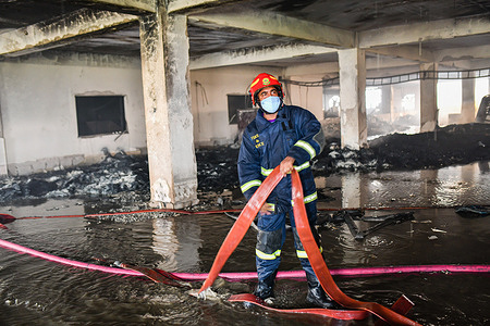Firefighter prepares to douse a fire that broke out a day before in a beverage and food factory in Rupganj Narayanganj district on the outskirts of Dhaka.At least 52 people have been killed, 25 others injured and many are feared trapped after a massive fire raged through a factory, the cause of the fire which originated at a ground floor of a multi storey building of the factory is not yet known.