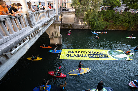 """Protesters on stand-up paddleboards, kayaks and canoes on the river Ljubljanica pull a large banner that says """"Protect the water. Vote no!"""" during the demonstration. Friday's anti-government protests against government's proposed changes to the water act encouraging the public to vote against the act at a referendum taking place on July11."""