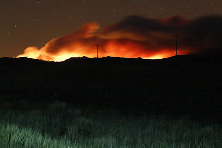 Flames illuminate the smoke rising from the Beckwourth complex fire.The Beckwourth Complex fire continues to burn through the night.