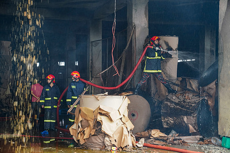Firefighters extinguish a fire at the ground floor of a burnt Hashem Foods Limited factory in Rupganj, Narayanganj district on the outskirts of Dhaka.A massive fire in a Bangladesh food processing factory has killed at least 52 people trapped by flames that forced many workers to leap for their lives from the upper floors, citing police officials.