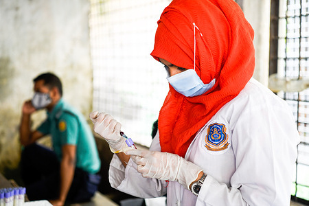Nurse collects a blood sample to cross-match DNA with victims who died after a fire broke out at a Hashem Foods Ltd factory in Rupganj, Narayanganj district, on the outskirts of Dhaka.At least 52 people have been found dead, 25 others injured and many are feared trapped after a massive fire raged through a factory, the cause of the fire which originated at a ground floor of a multi-storey building of the factory is not yet known.