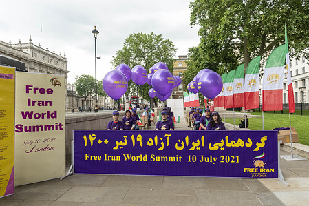 Activists wearing Free Iran T-shirts and caps prepare to watch the largest international event dedicated to justice and human rights in Iran during the annual Free Iran World Summit.  The event is hosted by Iran Freedom, a network for Iranian liberation.
