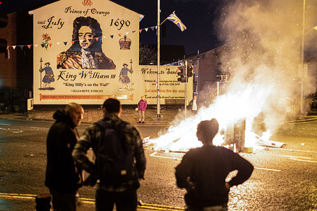 """A fire lit in the middle of the street in front of a mural depicting William of Orange in South Belfast. July 11th or 'Eleventh Night' sees a night of bonfires which are lit at midnight around the North of Ireland to celebrate the turning of July 12th. This year marks the centenary of the formation of Northern Ireland and is also the first permitted Orange marches since the beginning of the pandemic. The marching season has fallen during a tense period when Brexit protocols are causing political debate and community divide threatening a return to a volatility not seen since the times of """"the Troubles""""."""