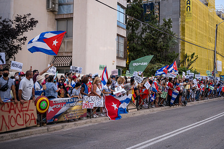 Protesters seen waving flags during the demonstration. Dozens of people demonstrate in front of the Cuban embassy in Madrid for the second consecutive day under the slogan #SOSCuba against the Cuban communist regime.