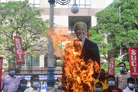 SUCI party members burn an effigy of U.S president Joe Biden in front of the American Consulate during the demonstration. Socialist Unity Centre of India (SUCI) party members rally against the ongoing protest in Cuba, a protest against the Communist Government of Cuba. According to the SUCI party the protest is happening due to the sanctions imposed on Cuba by the U.S government.