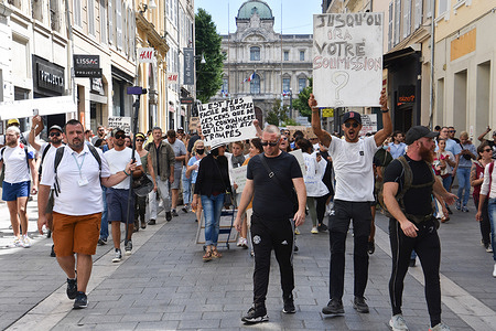 """Protesters hold placards during the demonstration against the health pass in Marseille. French President Emmanuel Macron announced among new anti-Covid 19 measures a """"health pass"""" which will be necessary to be frequenting café terraces, restaurants, cinemas, theatres and other culture and leisure activities to help contain the spread of the Covid-19 virus."""