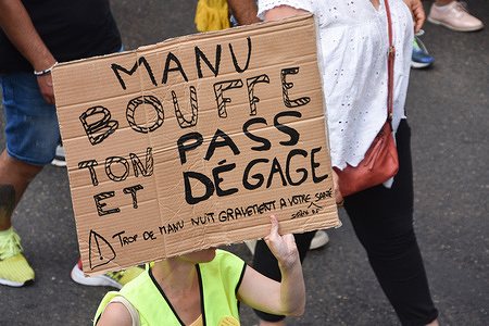 """A protester holds a placard during the demonstration against the health pass in Marseille.French President Emmanuel Macron announced among new anti-Covid 19 measures a """"health pass"""" which will be necessary to be frequenting café terraces, restaurants, cinemas, theatres and other culture and leisure activities to help contain the spread of the Covid-19 virus."""