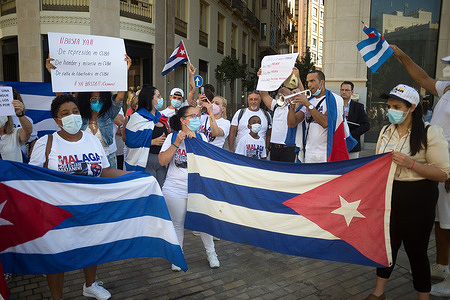 Protesters seen holding Cuban flags and placards as they take part in a demonstration in support of Cuban population at Marques de Larios street.A group of Cuban residents in Malaga have marched along main streets in downtown under the slogan: 'Homeland and life' to demonstrate against government of Cuban president Miguel Diaz Canel, after social breakdown in Cuba demanding the end of the communist dictatorship.