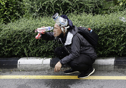 A protester washes his face with water as riot policemen fire tear gas, during the demonstration outside Government House.Police in Bangkok fired water cannons, rubber bullets and tear gas at pro-democracy protesters demanding Prime Minister, Prayut Chan-o-cha steps down and the government be held accountable for its gross mismanagement of the Covid-19 pandemic.