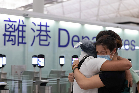 """A girl cries in her friends' arms as her friend departs, at Hong Kong international airport a day before the deadline of """"Leave outside the Rules"""" (LOTR) for BN(O) passport holders, as a special allowance for HongKongers to apply for visa after landing in UK. Thousands of HongKongers are expected to leave for the UK, as the city has been facing intensifying crackdown on human rights and freedom following China's National Security Law, with impacts on its economy amid the COVID-19 pandemic and adding pressure from China government. BN(O) - British National (Overseas)"""
