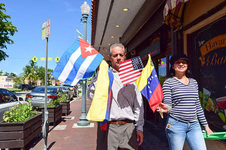A couple marching with the flags of Cuba, Venezuela and the United States, during a demonstration in favour of Cuban freedom in La Pequena Habana.