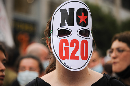"""A protester wears a mask with """"No G20"""" written on it during the demonstration. A network called """"BeesAgainstG20"""", including several environmentalist associations and green movements, such as Friday for Future staged a protest in Piazza Dante (Dante Square) against the G20 Environment, Climate, and Energy Meeting in Naples."""