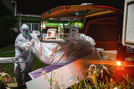 (EDITORS NOTE: Image depicts death) Siam Nonthaburi foundation staff members carry the body of a COVID-19 victim to a coffin at Klong Luang hospital in Pathum Thani. As the death toll from COVID-19 in Thailand continues to rise, the Siam Nonthaburi foundation is operating a free service for transferring Covid 19 victims to crematoriums. In July, they have already transferred 240 people for cremation at temples around Nonthaburi.