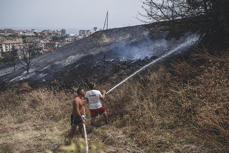 Men seen trying to extinguish a fire. Wildfires burned the hill near Viale Europa, in Catanzaro Lido, siding the road leading to Catanzaro Regional Citadel. In the last week more than 110 fires related emergencies hit the region, causing also 5 deaths.