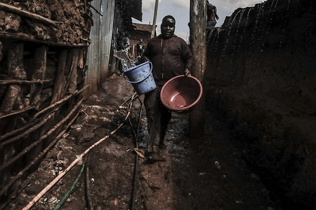 A resident runs with a bucket of water to help put out a fire that razed twelve homes in Bombolulu, Kibera. Residents joined hands to help put out a fire that occurred today afternoon from tangled electric wires supplying power to different homes. The fire razed down twelve homes and properties leaving most residents stranded.