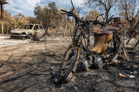 View of a burnt motorcycle and a car near Agia Anna. The aftermath of the wildfires in the northern part of the Greek island of Evia (Euboea ) where fire kept burning almost for 10 days, burning forest and buildings. Almost 100,000 hectares of forest burned in Greek fires according to Copernicus European Emergency Services.