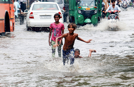 Children playing on a waterlogged street after heavy rainfall at Jahangirpuri area in New Delhi.Due to the Heavy rainfall leading to water logging in many areas, Delhi Traffic Police closed several underpasses and road to avoid traffic jams for the commuters. Indian Meteorological Department (IMD) announced thunderstorms and rain continue in the National Capital.