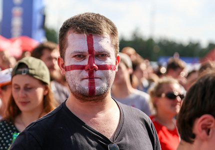 A fan of the England national team seen with his face painted in the colors of the national flag.