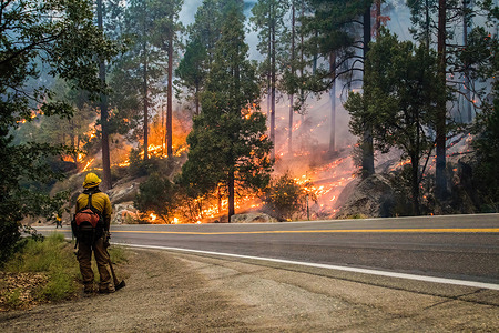 A firefighter monitors the Caldor fire as it burns by the highway.The Caldor fire has grown to over 122,000 acres and threatens to grow to the Tahoe basin.