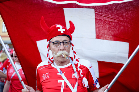 A Swiss fan parading with a flag and a   fancy dress costume. He was among hundreds of Swiss football fans who walked the streets in the city center before the game between switzerland and Costa Rica.