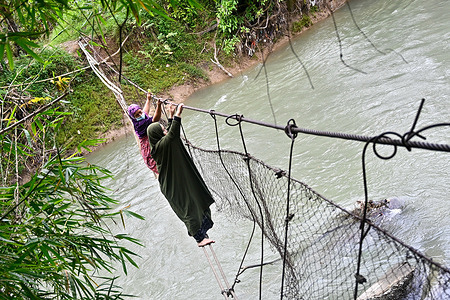 Two residents cross a river using a badly damaged bridge in Malela. Even though it is dangerous, every day the bridge that has been damaged by the flood is still used by residents to cut travel time to other villages.