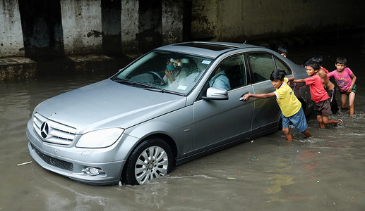 Kids seen pushing a car through a waterlogged Zakhira underpass area after heavy rainfall in New Delhi.Delhi Traffic Police closed several underpasses and roads to avoid traffic due to heavy rainfall and water logging in many areas including Indira Gandhi International Airport. Indian Meteorological Department (IMD) announced thunderstorms with very heavy intensity rain in the Capital.
