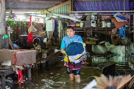 Lopburi resident is seen carrying his cloths from his house during theaftermath.After Dianmu storm, 20 provinces got affected. Thai government also announced that more than 55,000 households were affected by floods. Lopburi is one of the affected provinces and that the situation is closely monitored.