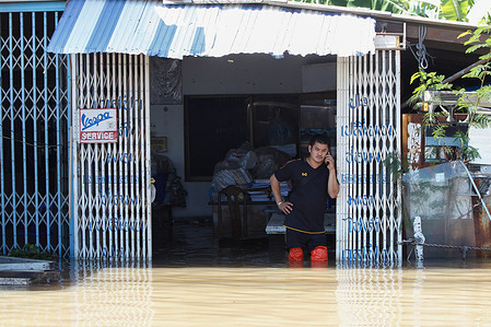 A man uses his mobile phone in a flooded house as Pasak Jolasid Dam overflows. According to the Royal Irrigation Department (RID), tropical storm Dianmu and an active low-pressure cell caused widespread flooding. About 515 million cubic metres of runoff was expected to flow into the Pasak Jolasid Dam between Sept 27th. and Oct 3rd. If the discharge rate remained at 8.64 million cubic metres a day, the dam would reach capacity on Sept 30th.