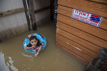 A kid swimming in flooded water during the aftermath. After tropical Dianmu storm, a widespread of floods in 30 provinces in Central and North East of Thailand occurred. The government announced that the situation must be closely monitored day by day.