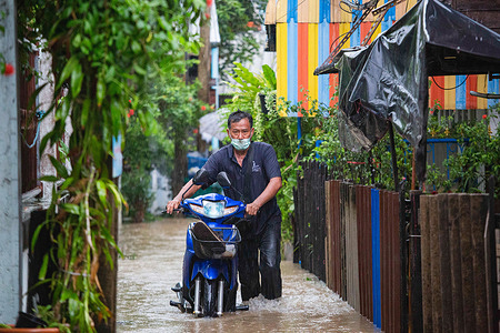 Koh Kret resident walks through a submerged alley with his motorcycle. Twenty provinces have been affected by the Dianmu storm.Each day the riverside communities in Nonthaburi face renewed flooding.