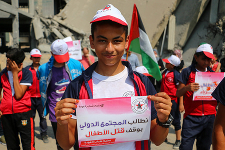 A Palestinian children seen holding a placard in protest against the killing of the Palestinian children by the Israeli forces occupation in Gaza.  The 'Palestinian Democratic Youth Union' organized a protest against the policy of Israel in front of the battalion building destroyed by the Israeli forces occupation west of Gaza City.