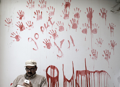 United Nations Relief and Works Agency for Palestine Refugees (UNRWA) employee seen sitting from of a painted wall as he take part in a protest against job cuts announced by the agency's headquarters in Gaza City. UNRWA announced today that it was cutting more than 250 jobs in the Palestinian territories after the United States held back hundreds of millions in aid.