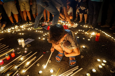 A child lights a candle during the vigil service .People gathered  outside the Hellenic Parliament in memory of the 91 victims of the deadly fire in  Eastern Attica , as they symbolically formed with candles a heart on the date (23/7) of the tragic event.
