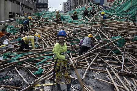 Workers remove bamboo scaffolding after it has collapsed, fallen and blocked the street. Super Typhoon Mangkhut aftermath is visible in most districts of Hong Kong. The super typhoon Mangkhut has passed next to Hong Kong on the 16th September causing large scale damages around the city, there are 432 people injured due to the storm with 2 still in critical condition.