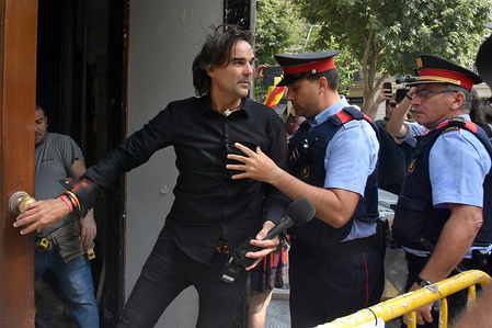Cake Minuesa  seen being escorted by the police. Cake Minuesa is a controversial media journalist working for OK DIARIO who has a right-wing political character.
